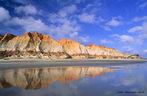 """Falésias são paredões íngremes encontrados no litoral de quase todo o mundo, esculpidos pela lenta mas constante ação da água do mar, através das ondas e marés, e também pela chuva, que após um longo período de tempo indo de encontro à rocha, acaba por """"esculpi-la"""", originando costas altas e abruptas, resultado direto da erosão marítima. Na imagem, as falésias da praia de Morro Branco, no Ceará.</br></br>Palavras-chave: Ambientes Costeiros. Falésias. Erosão. Intemperismo. Turismo."""