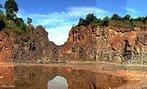 Frente de extração dos basaltos da Formação Serra Geral, com visão da base. Esta unidade, da Era Mesozóica - Período Cretáceo, registra o intenso vulcanismo que iria iniciar a separação dos continentes Africano, Sul-americano, Antártico, Australiano e Indiano, através do maior vulcanismo do tipo fissural ocorrido no globo, que originou a sequência Serra Geral. </br></br> Palavras-chave: Dimensão Socioambiental. Econômica. Território. Lugar. Região. Basalto. Rochas. Afloramento. Serra Geral. Relevo. Solo.