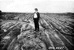 """A Lei Federal de número 7.876 instituiu 15 de abril como o Dia Nacional da Conservação do Solo. Tal data foi escolhida em homenagem ao nascimento do conservacionista estadunidense Hugh Hammond Bennett (1881–1960), considerado em seu país como o """"pai"""" da conservação do solo. Nesta foto ele aparece em uma área que perdeu cerca de 75% da camada superficial do solo devido à erosão, em Haskell (Oklahoma) em maio de 1943.</br></br>Palavras-chave: Erosão. Solo. Poluição. Agricultura. Agrotóxicos. Saúde. Doenças. Alimentos. Economia. Importação.Exportação. Deslizamentos."""